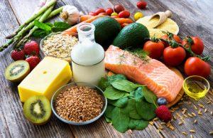 Gesunde Nahrungsmittel liegen auf einem Holztisch als Grundlage für einen gesunden Ernährungsplan